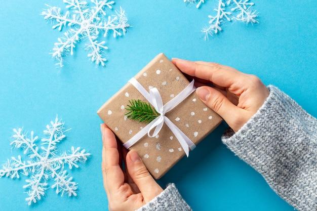 Kobiece ręce pod kątem z prezentem świątecznym w papierowym opakowaniu na niebiesko z dużymi płatkami śniegu
