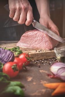 Kobiece ręce pokroić surową wieprzowinę na drewnianej desce w kuchni, proces gotowania mięsa z warzywami i przyprawami