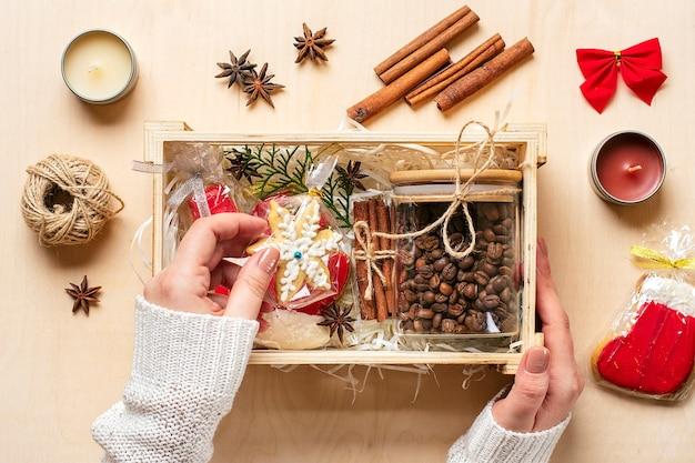 Kobiece ręce położyły pakiet pielęgnacyjny, sezonowe pudełko z kawą, piernikiem i cynamonem