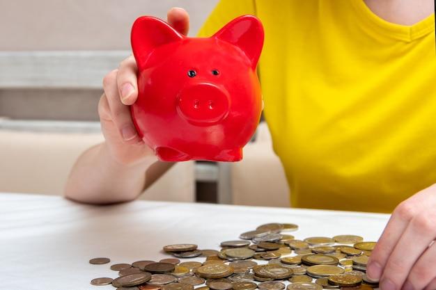 Kobiece ręce potrząsają skarbonką, aby sprawdzić zawartość, kilka monet leży na stole w domu.