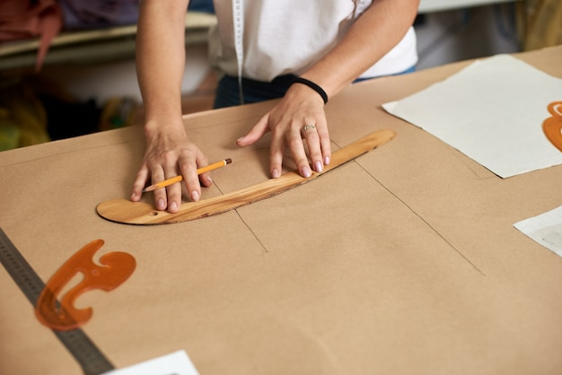 Kobiece ręce projektanta rysowanie linii na tekturze