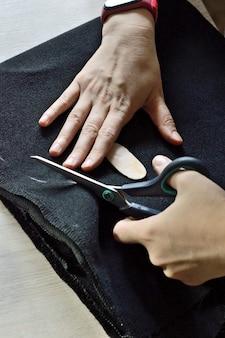 Kobiece ręce przecinają czarną tkaninę nożyczkami. zbliżenie.