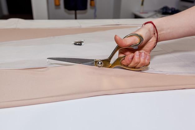 Kobiece ręce przecinają materiał nożyczkami krawieckimi na wzór papieru, na białym stole