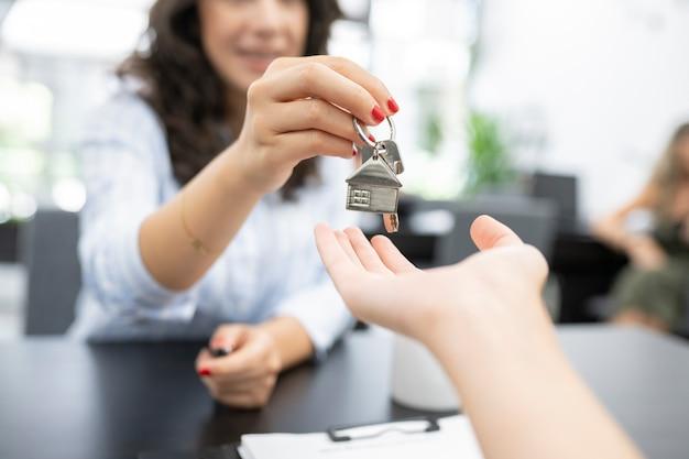 Kobiece ręce przekazują klucze kupującemu