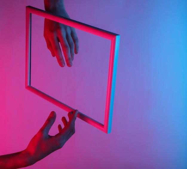 Kobiece ręce przez strzelistą ramkę z neonowym światłem holograficznym