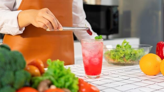 Kobiece ręce przygotowujące mocktail, wkładając słodką morwy do szklanki
