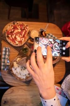 Kobiece ręce robi zdjęcia na stole smartfona z pyszną pizzą w restauracji. widok z góry