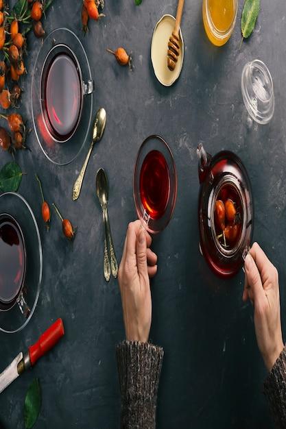 Kobiece ręce robią herbatę z dzikiej róży. widok z góry