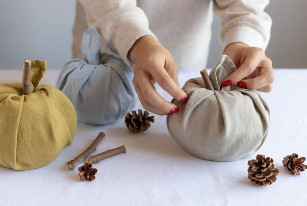 Kobiece ręce robiące dynie z tkaniny koncepcja święto dziękczynienia i halloween