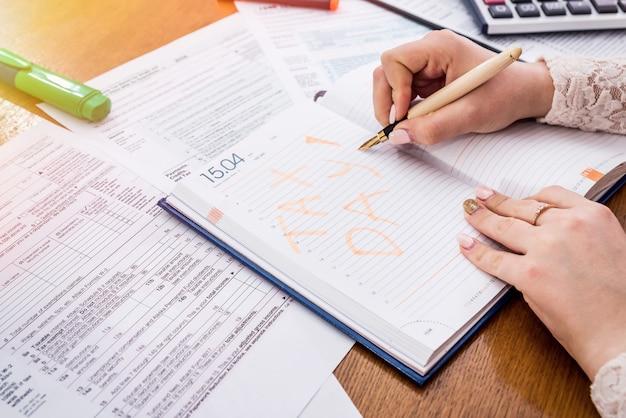 Kobiece ręce robiące notatkę o płaceniu podatków w pamiętniku