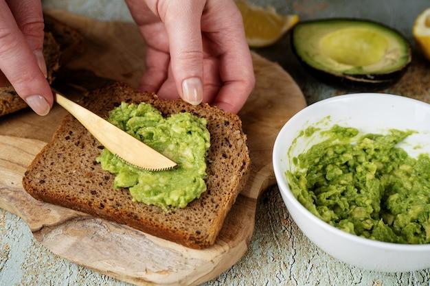 Kobiece ręce rozkładają tłuczone awokado na zdrowej kromce chleba. wysokie tłuszcze nasycone mogą pomóc w utrzymaniu zdrowego poziomu cholesterolu. zdrowe wegańskie jedzenie