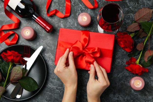 Kobiece ręce rozpakuj pudełko na czarnym tle z akcesoriami happy women's day