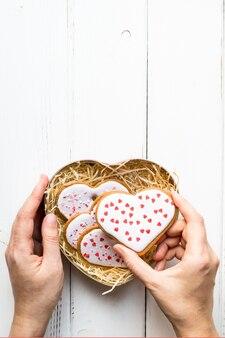 Kobiece ręce stawia domowe ciasteczka w kształcie serca w pudełko na prezent na walentynki na białym tle drewnianych