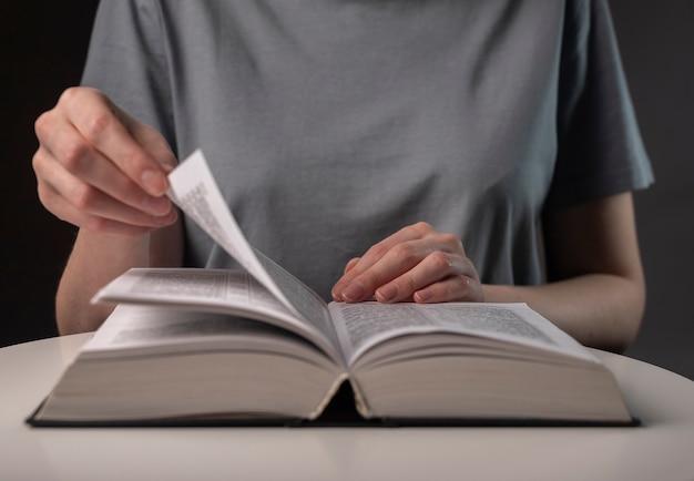 Kobiece ręce studenta z bliska, przewracając strony grubej książki, szukając informacji i czytając.