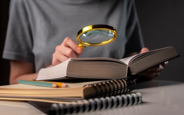 Kobiece ręce studenta z bliska, trzymając szkło powiększające i książkę lub podręcznik, wyszukiwanie informacji i czytanie w nocy.