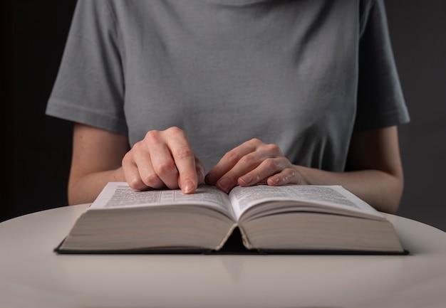 Kobiece ręce studenta z bliska, wskazując na tekst w książce lub podręczniku, szukając informacji i czytając w nocy.