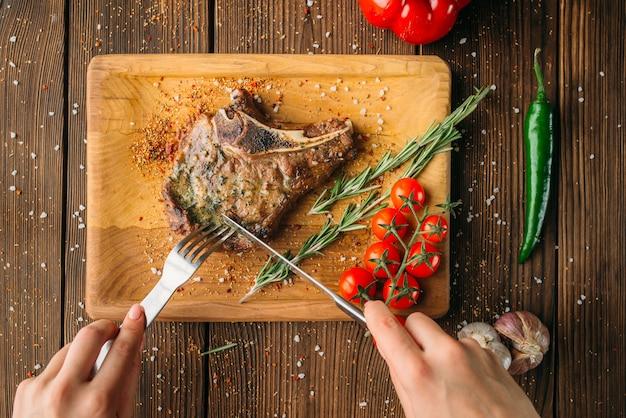 Kobiece ręce tnie kawałek soczysty stek, widok z góry, drewniany stół na tle. jedzenie świeżej wołowiny, jedzenie z grilla