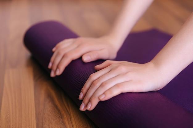 Kobiece ręce toczące niebieską matę do ćwiczeń po podłodze po zakończeniu treningu w klubie studio jogi lub w domu