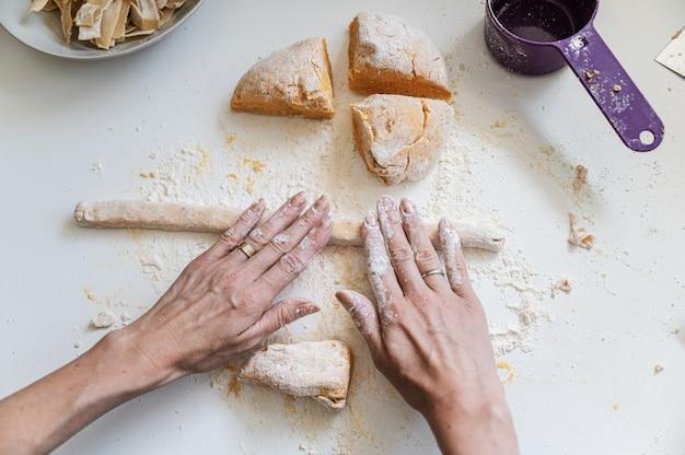 Kobiece ręce toczenia ciasta makaronowego
