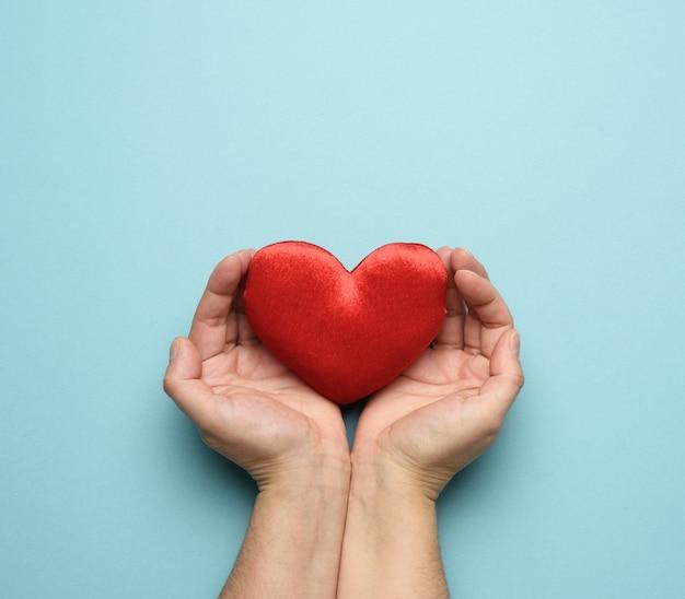 Kobiece ręce trzyma czerwone serce włókienniczych, niebieskie tło. koncepcja miłości i darowizny, z bliska