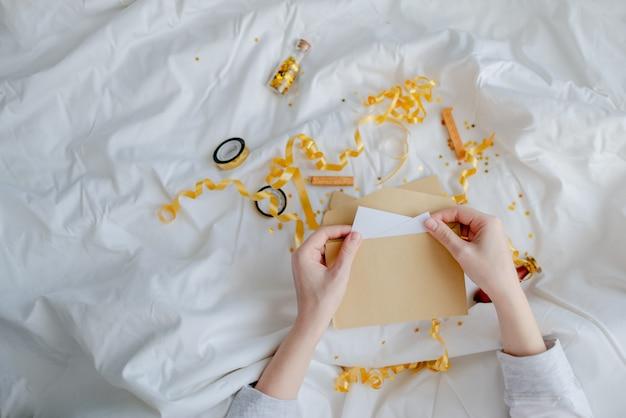 Kobiece ręce trzyma kartę podarunkową, kopertę i pudełko na koc nad łóżkiem. koncepcja nowego roku i święta. widok z góry w poziomie