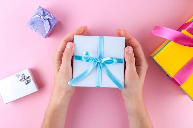 Kobiece ręce trzyma małe białe pudełko ozdobne owinięte niebieską wstążką. dawać i otrzymywać prezenty od bliskich.