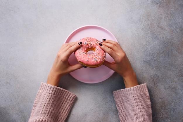 Kobiece ręce trzyma pączek na różowy talerz na tle kamienia.