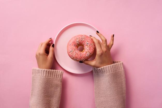 Kobiece ręce trzyma pączek na talerzu na różowym tle.