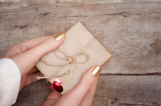 Kobiece ręce trzyma prezent.