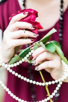 Kobiece ręce trzyma różę, perłę