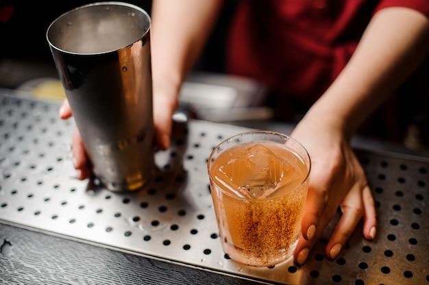 Kobiece ręce trzyma shaker i kieliszek koktajlowy ozdobiony cynamonem