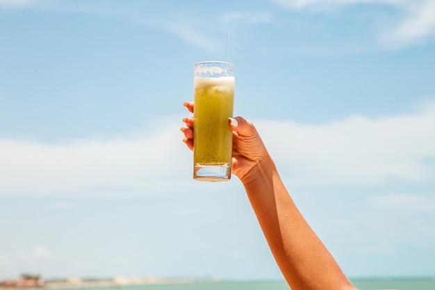 Kobiece ręce trzyma sok ananasowy z plażą w tle.