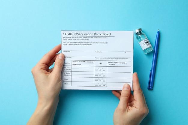 Kobiece ręce trzymać kartę szczepień na niebieskim tle