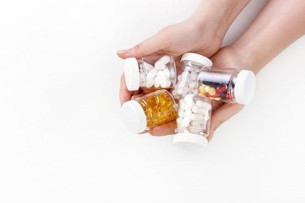 Kobiece ręce trzymać wielobarwne pigułki na białej powierzchni. widok z góry. koncepcja zdrowia.
