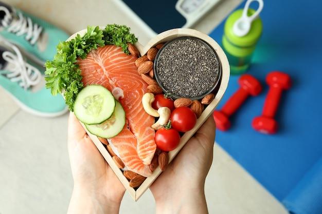 Kobiece ręce trzymać zdrową żywność w sercu, widok z góry