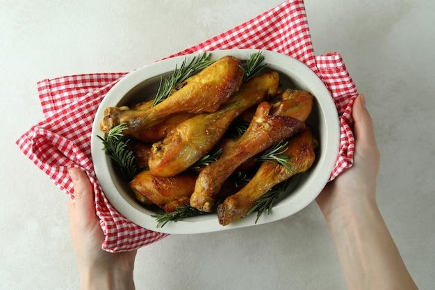 Kobiece ręce trzymają blachę do pieczenia z podudziami pieczonego kurczaka
