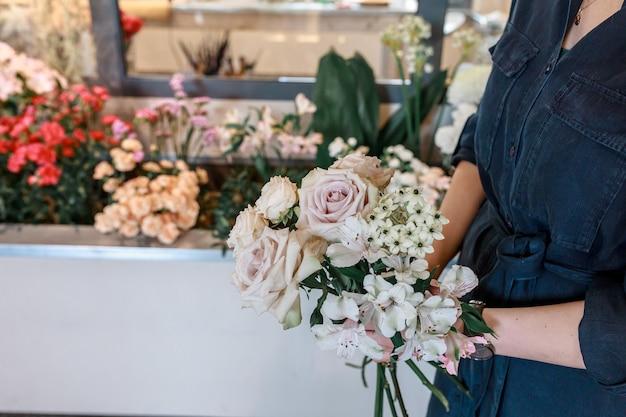 Kobiece ręce trzymają bukiet kwiatów. jasnobeżowe róże. koncepcja kwiaty jako prezent na rocznicę.