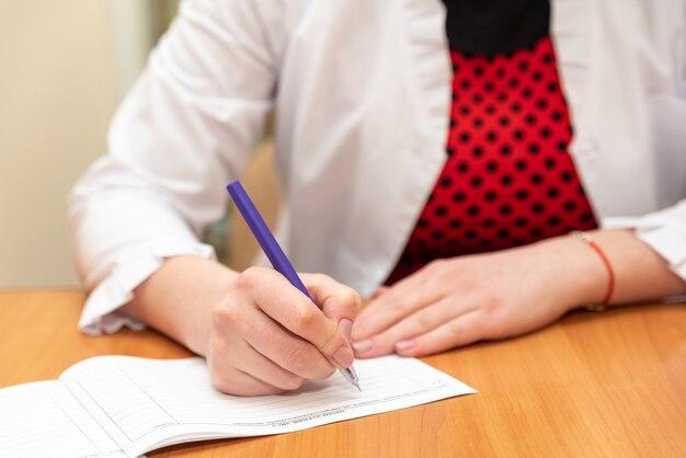 Kobiece ręce trzymają długopis, a lekarz pisze na papierze biały płaszcz