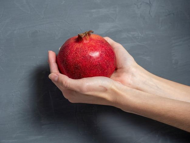 Kobiece ręce trzymają dojrzały soczysty owoc granatu cały na szarym tle. zdrowe i smaczne owoce.