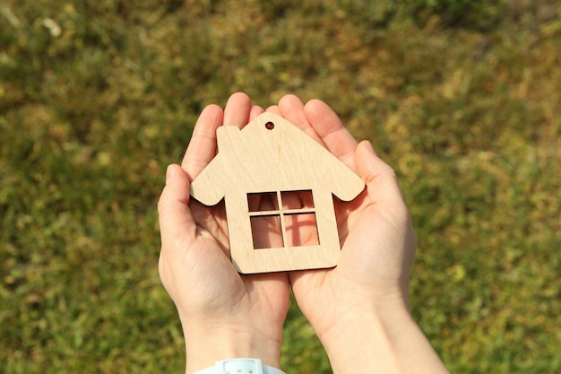 Kobiece ręce trzymają drewniany dom. kupno nieruchomości