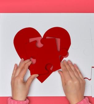 Kobiece ręce trzymają duże białe puzzle z kawałkiem czerwonego serca