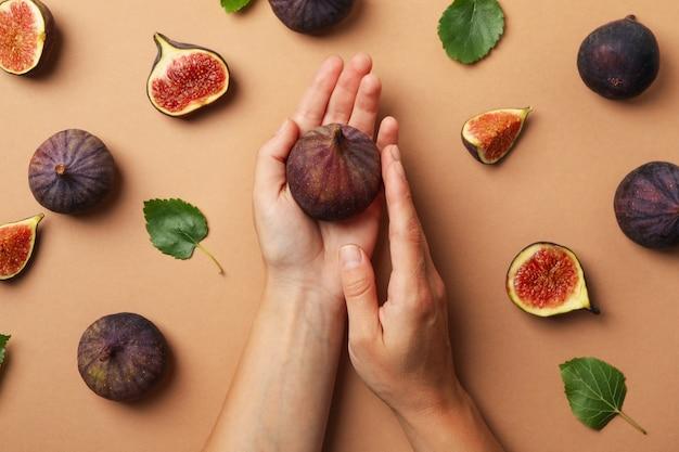 Kobiece ręce trzymają figę na statku z owocami i liśćmi figi, widok z góry