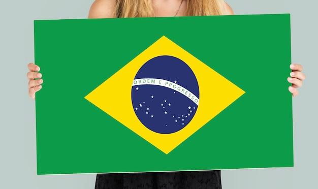 Kobiece ręce trzymają flagę brazylii patriotyzm