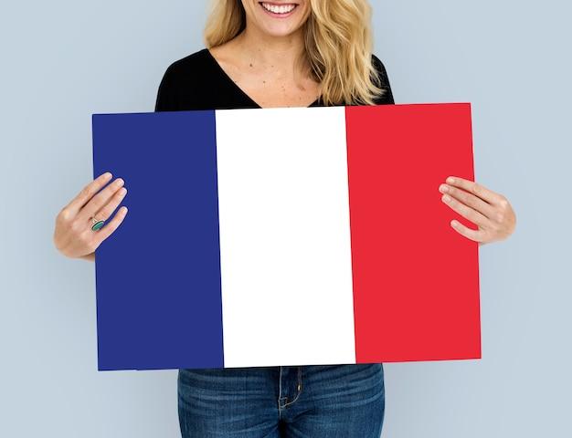 Kobiece ręce trzymają francuską flagę francji patriotyzm
