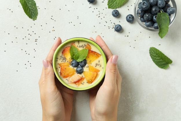 Kobiece ręce trzymają jogurt brzoskwiniowy na białym tle z teksturą