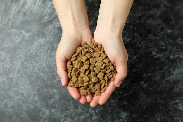 Kobiece ręce trzymają karmę dla zwierząt domowych na czarnym smokey