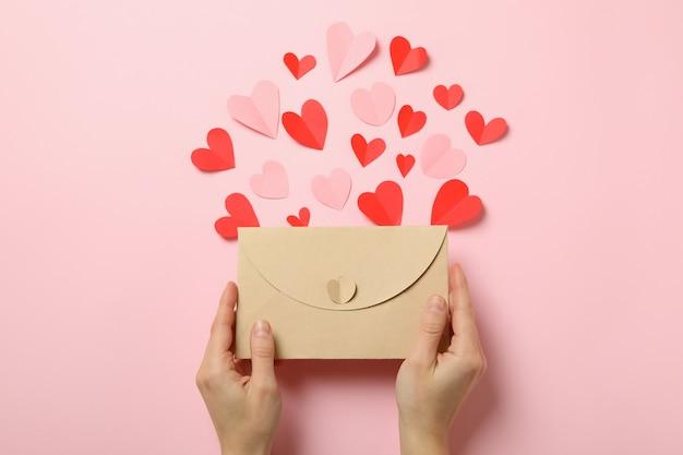 Kobiece ręce trzymają kopertę na różowym tle z ozdobnymi sercami