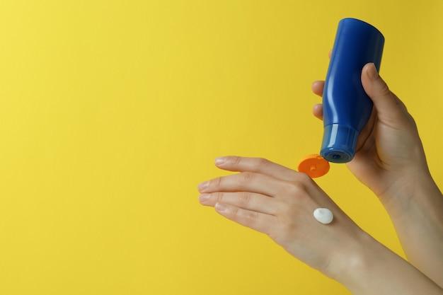 Kobiece ręce trzymają krem do opalania na żółtym tle na białym tle