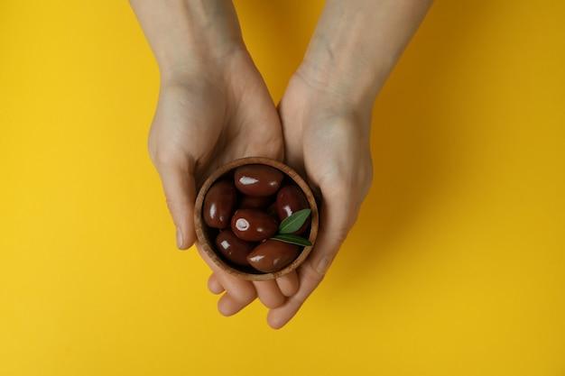 Kobiece ręce trzymają miskę czerwonych oliwek