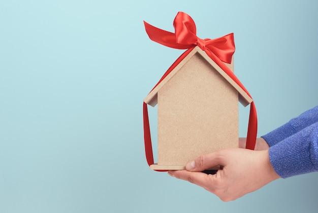 Kobiece ręce trzymają model drewnianego domu przewiązanego czerwoną jedwabną wstążką, pojęcie zakupu nieruchomości, hipoteka. skopiuj miejsce